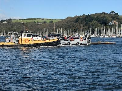 An image of the Dartmouth Lower Ferry tugboat and platform crossing the River Dart Estuary
