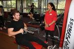 Leisure Centre gym with man wearing black leisure clothes on a rowing machine with a staff member standing advising wearing black trousers and red polo shirt.