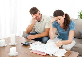a man and a woman looking through paperwork with worried expressions.