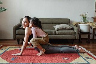 A mother and child doing a yoga pose on the floor of a living room, with a sofa visible in the background.