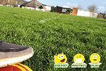 Large recreation park with green grass and foot resting on a football