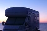 Motorhome parked next to sea at sunrise