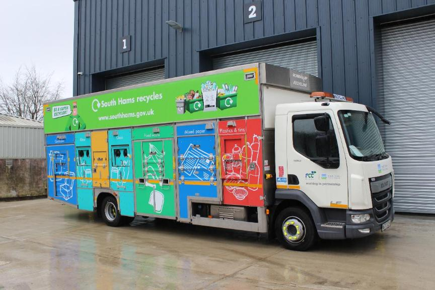Small green recycling vehicle with four sorting compartments